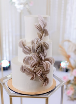Vue rapprochée avant du beau gâteau de mariage minimaliste en crème de couleur blanche décorée d'un décor de pétales de rose