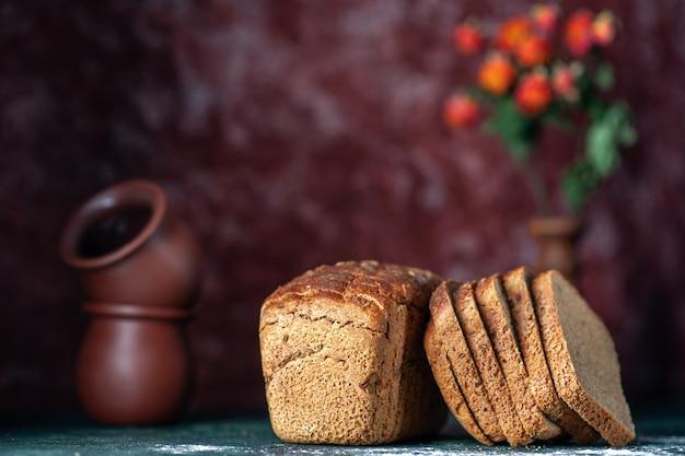 Vue rapprochée avant du pot de fleur de pain noir diététique sur fond de couleurs marron bleu