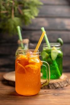 Vue rapprochée avant de l'eau de désintoxication et du jus de fruits frais dans des bouteilles avec des tubes sur fond de bois marron
