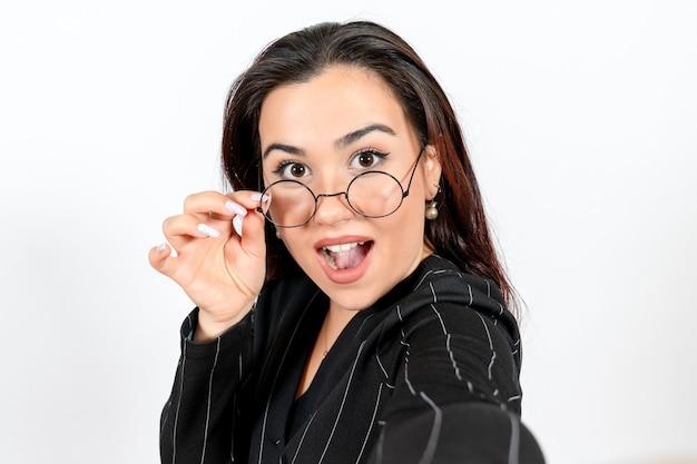 Vue rapprochée avant employé de bureau féminin en costume noir strict posant sur blanc