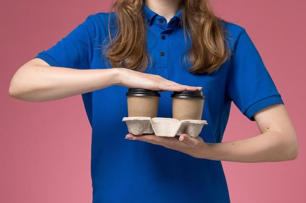 Vue rapprochée avant femme courrier en uniforme bleu tenant des tasses de café de livraison marron sur fond rose travail de l'entreprise uniforme de service