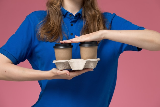 Vue rapprochée avant femme courrier en uniforme bleu tenant des tasses de café de livraison marron sur l'uniforme de service de bureau rose offrant des emplois