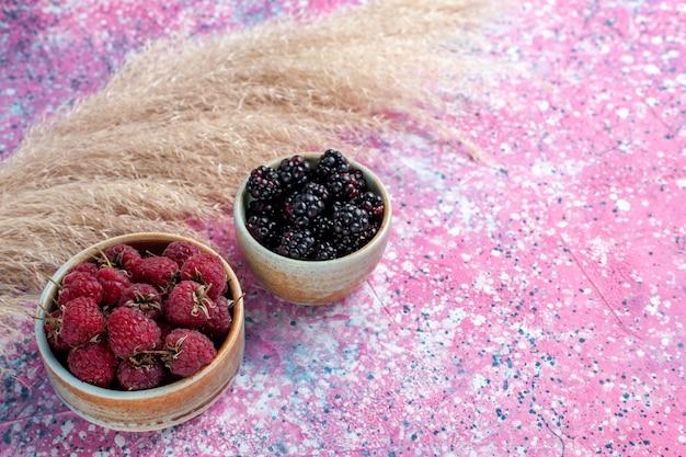 Vue rapprochée avant framboises et mûres à l'intérieur de petits pots sur fond rose clair.