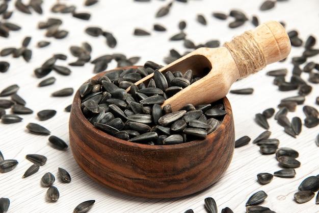Vue rapprochée avant graines de tournesol fraîches graines noires sur fond blanc huile de collation de maïs graine beaucoup de photo