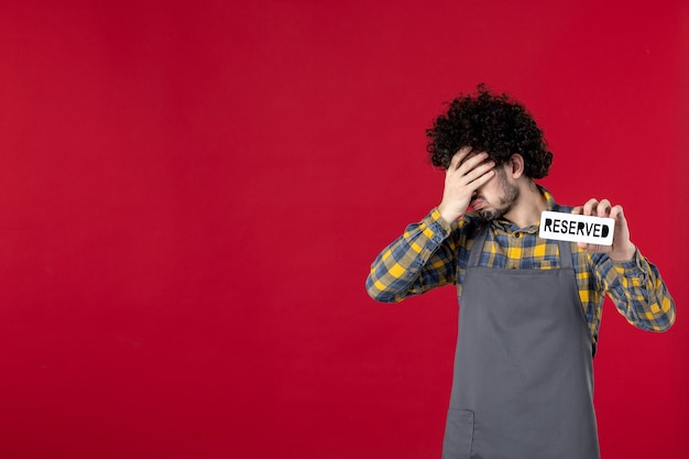 Vue rapprochée avant d'un homme fatigué avec des cheveux bouclés montrant une icône réservée sur fond rouge isolé