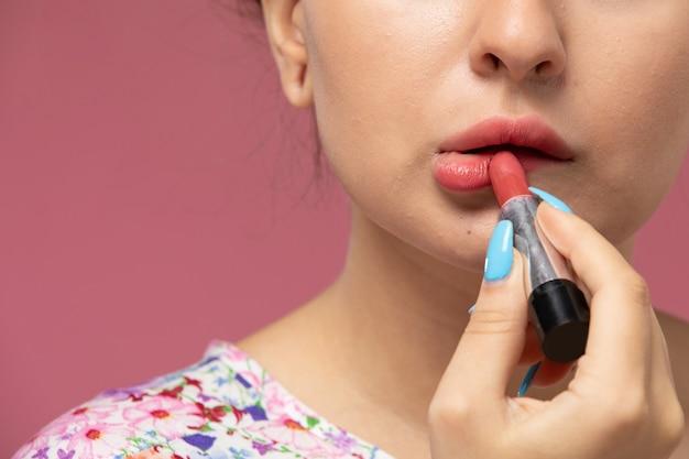 Vue rapprochée avant jeune femme en chemise conçue de fleurs faisant du maquillage sur le fond rose