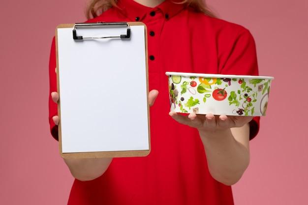 Vue rapprochée avant jeune femme courrier en uniforme rouge et cape tenant le bol de livraison et le bloc-notes sur le mur rose, la livraison uniforme de l'emploi de service
