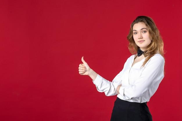 Vue rapprochée avant d'une jeune serveuse confiante papillon sur le cou et faisant un geste correct sur le côté droit sur fond rouge