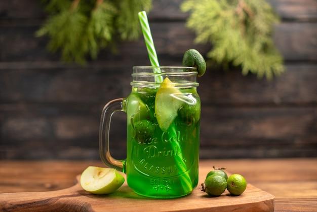 Vue rapprochée avant de jus de fruits frais dans un verre servi avec des tubes et des feijoas de citron vert sur une planche à découper en bois sur une table marron