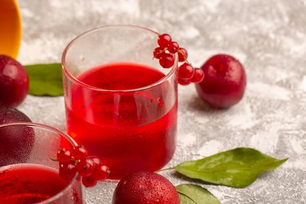Vue rapprochée avant de jus de prune rouge avec des prunes fraîches sur la surface claire