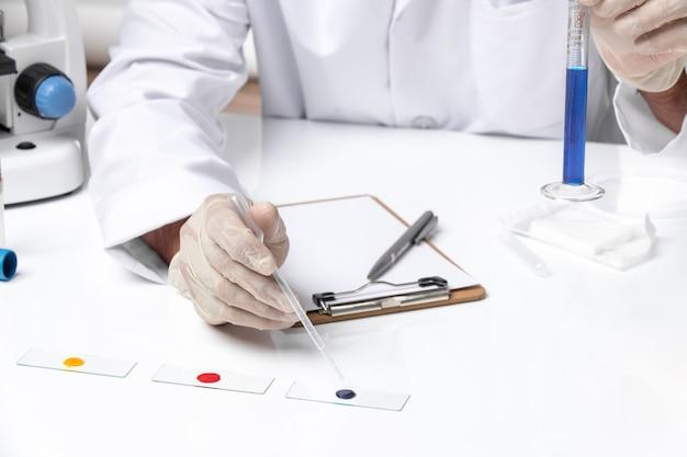 Vue rapprochée avant médecin de sexe masculin en costume médical blanc sur un bureau blanc