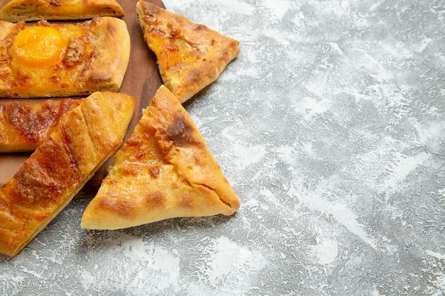 Vue rapprochée avant d'oeufs en tranches cuire de délicieuses pâtisseries avec des assaisonnements sur l'espace blanc
