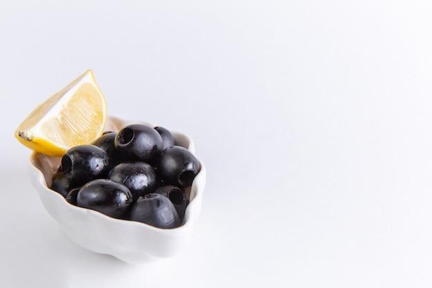 Vue rapprochée avant d'olives noires fraîches avec tranche de citron sur la surface blanche photo couleur huile végétale alimentaire