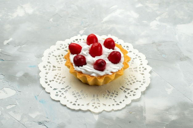 Vue rapprochée avant petit gâteau délicieux avec de la crème et des fruits rouges sur la surface légère du thé sucré
