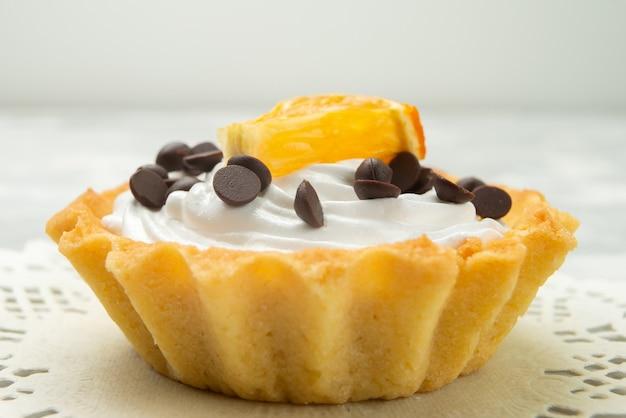 Vue rapprochée avant petit gâteau délicieux avec de la crème et des pépites de chocolat sur la pâte sucrée de surface légère
