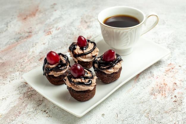 Vue rapprochée avant de petits gâteaux délicieux avec glaçage au chocolat et tasse de thé sur une surface blanche gâteau biscuit thé sucré au cacao