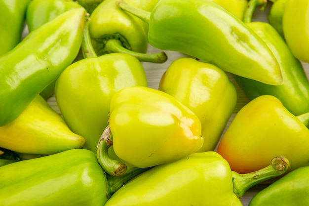 Vue rapprochée de l'avant des poivrons verts sur la couleur blanche des plantes de repas mûrs photo salade de poivrons végétaux