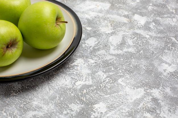 Vue rapprochée avant de pommes vertes fraîches à l'intérieur de la plaque sur la surface blanche de la vitamine de fruits mûrs mûrs frais