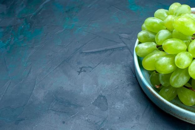 Vue rapprochée avant de raisins verts frais fruits moelleux et juteux à l'intérieur de la plaque sur le bureau bleu foncé.