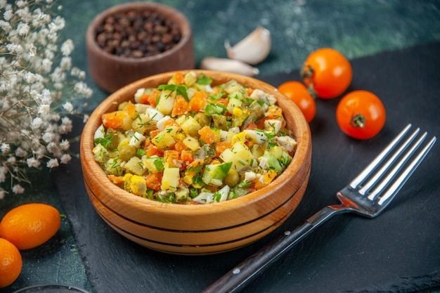 Vue rapprochée avant salade de légumes à partir d'ingrédients bouillis à l'intérieur de petite assiette sur fond sombre