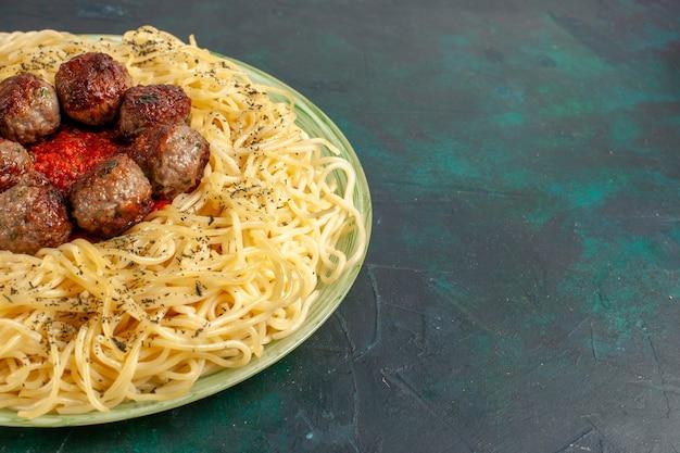 Vue rapprochée avant de savoureuses pâtes italiennes avec des boulettes de viande sur la surface bleu foncé