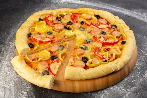 Vue rapprochée avant de savoureuses pizzas au fromage avec tomates rouges, olives noires et saucisses sur la surface sombre