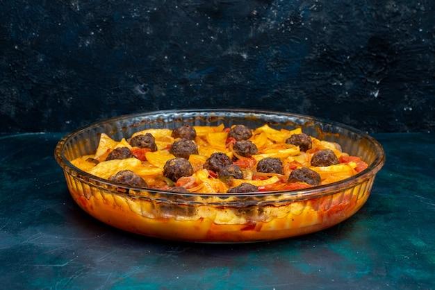 Vue rapprochée avant de savoureux repas de pommes de terre avec des boulettes de viande et des tomates sur fond bleu foncé.