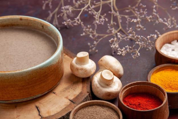 Vue rapprochée avant de la soupe aux champignons savoureuse avec différents assaisonnements sur l'espace violet foncé