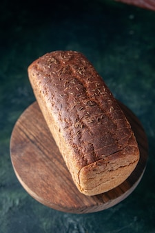 Vue rapprochée avant de tranches de pain noir sur planche de bois sur fond de couleurs mélangées en détresse