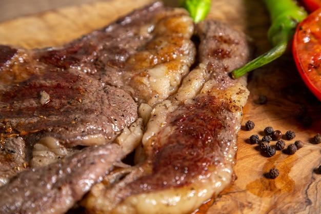 Vue rapprochée avant de la viande cuite frite avec des légumes frits sur la surface en bois