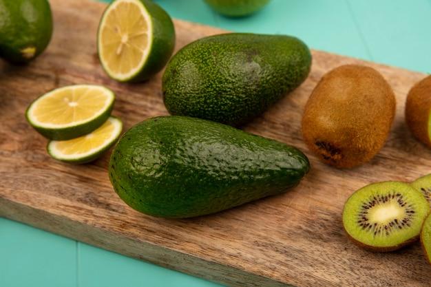 Vue rapprochée d'avocats frais avec limes et kiwis isolés sur une planche de cuisine en bois sur fond bleu