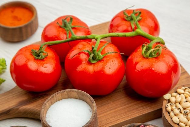 Vue rapprochée en bas de la branche de tomate sur une planche à découper le curcuma salé sur une table grise