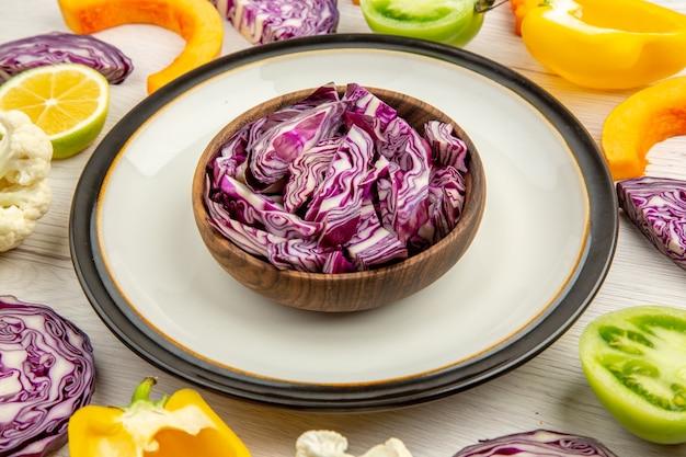 Vue rapprochée en bas des choux rouges coupés dans un bol sur un plateau rond coupé des légumes sur une surface blanche