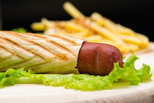Vue rapprochée sur bâton de pain farci de saucisses assis sur une feuille de laitue tandis que tas de frites se trouve en arrière-plan