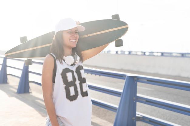 Vue rapprochée d'une belle fille avec sa longue planche de skateboard au coucher du soleil