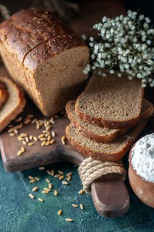 Vue rapprochée des blés de pain noir diététique sur une planche à découper en bois farine d'oeufs de fleur dans un bol sur fond bleu