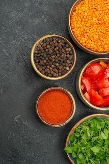 Vue rapprochée des bols de lentilles d'herbes de lentilles tomates épices poivre noir