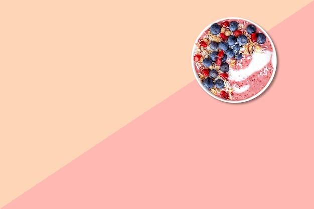 Vue rapprochée de la bouillie de blé aux myrtilles isolées sur fond rose.