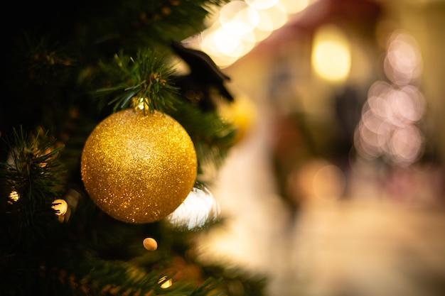 Vue rapprochée de la boule d'or comme décoration accrochée aux branches d'un arbre de noël et scintillant au soleil.