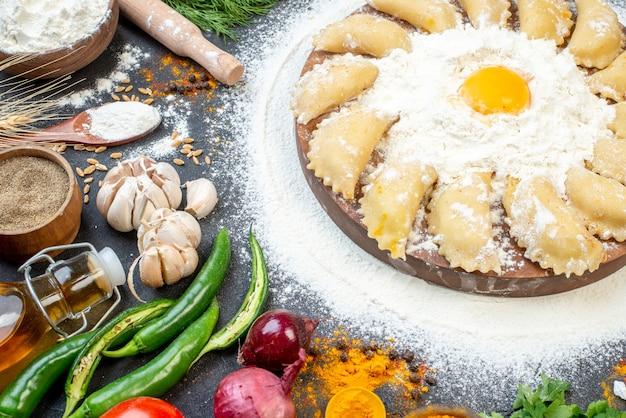 Vue rapprochée de boulettes crues à bord autour de la farine et d'un ensemble d'aliments sur une surface de couleur sombre