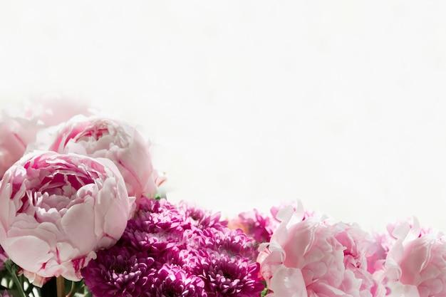 Vue rapprochée d'un bouquet de pivoines roses et de chrysanthèmes sur fond blanc. fond de concept, fleurs, vacances.