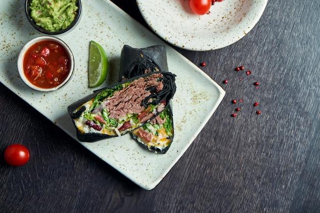 Vue rapprochée sur burrito avec boeuf, riz, tomates, maïs et poivron en pita noir sur une plaque brune avec salsa de tomates et guacamole. rouleau de shawarma végétarien