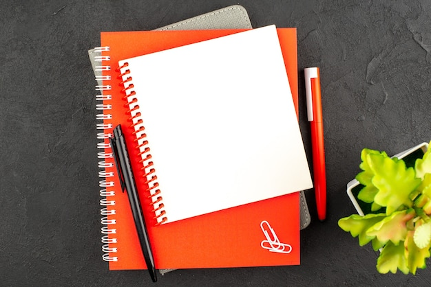 Vue rapprochée de cahiers à spirale fermés de différentes tailles et de stylos pot de fleurs sur fond noir
