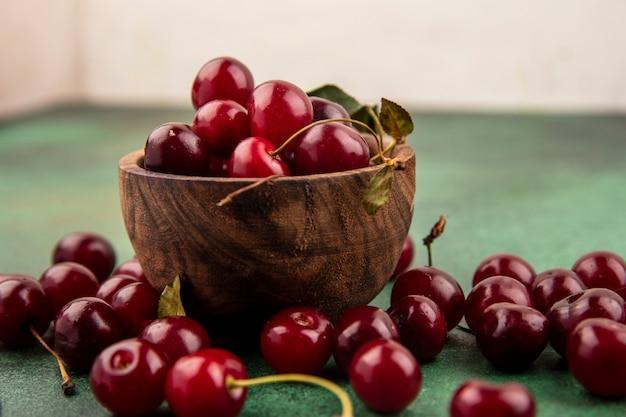 Vue rapprochée de cerises dans un bol en bois et sur une surface verte et fond blanc