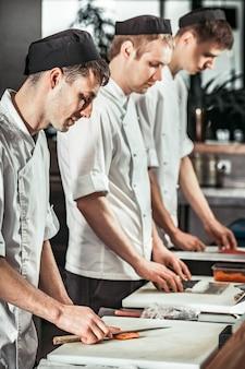 Vue rapprochée, les chefs cuisinent les sushis.