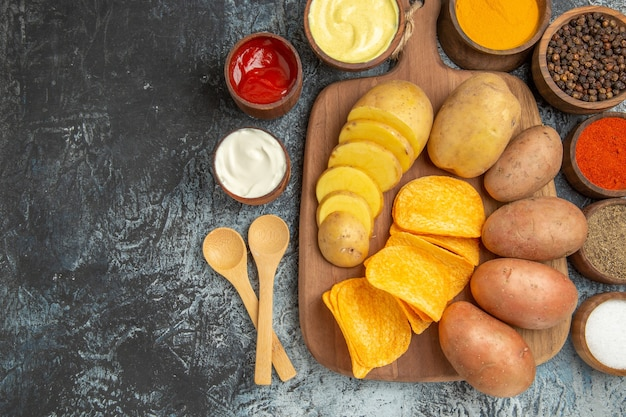 Vue rapprochée de chips croustillantes et pommes de terre non cuites sur une planche à découper en bois et différentes épices sur table grise