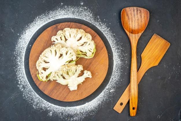 Vue rapprochée des choux-fleurs frais sur une planche à découper ronde et des cuillères en bois sur une surface de couleur sombre