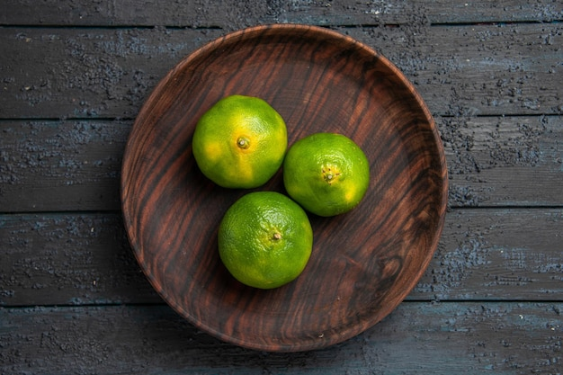 Vue rapprochée des citrons verts sur une assiette de trois citrons verts au centre de la table sombre