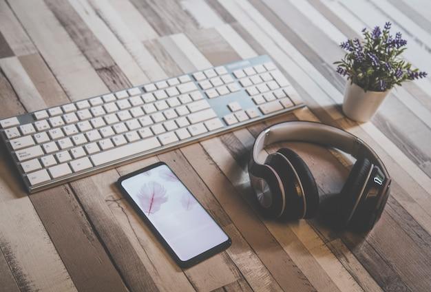 Vue rapprochée d'un clavier de pc blanc avec un téléphone portable avec un économiseur d'écran de plumes roses et un casque