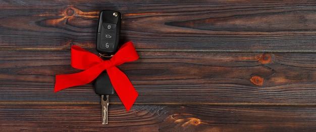 Vue rapprochée des clés de la voiture avec l'arc rouge comme présent sur fond en bois